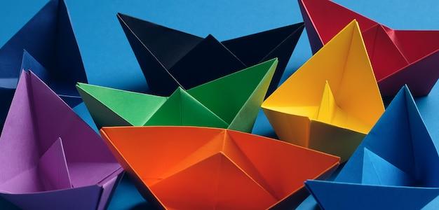 Bunte papierboote auf einem hellen blauen hintergrund. speicherplatz kopieren Premium Fotos