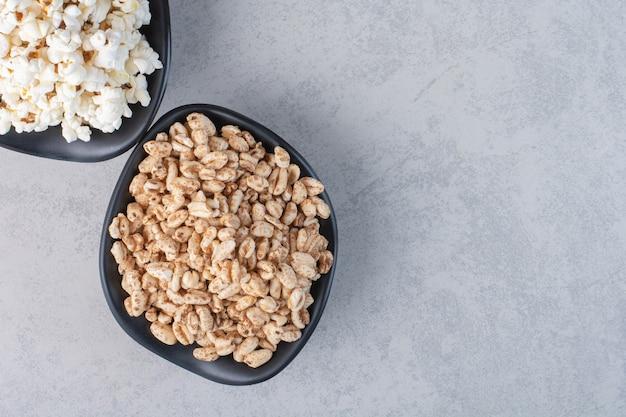 Bunte schalen voller popcorn-bonbons und verstreutem popcorn um einen mit stoff bedeckten sockel auf marmor. Kostenlose Fotos