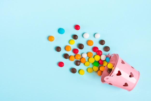 Bunte schokoladenbonbons wurden aus eimer mit herzen auf blauer flacher lage heraus verschüttet Premium Fotos