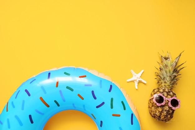 Bunte sommerflachlage mit blauem aufblasbarem kreisdonut, lustige ananas in der sonnenbrille Premium Fotos