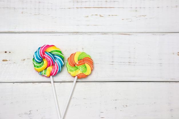 Bunte süßigkeiten auf holztischhintergrund. draufsicht mit kopienraum Premium Fotos