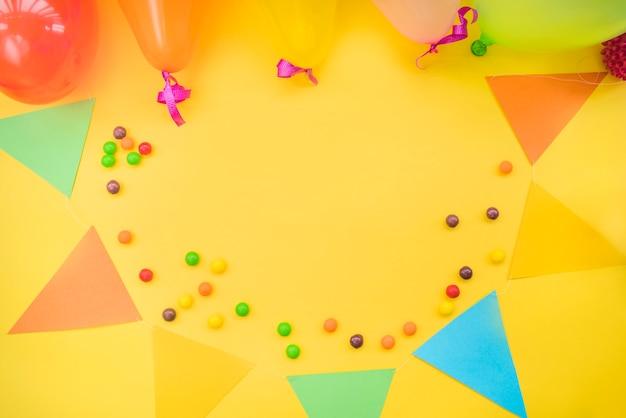 Bunte süßigkeiten mit flagge und ballonen auf gelbem hintergrund Kostenlose Fotos