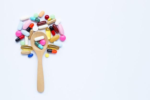 Bunte tabletten, kapseln und pillen mit hölzernem löffel auf weiß Premium Fotos