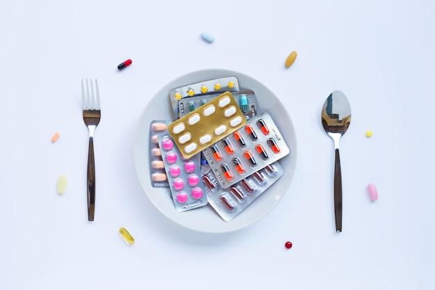 Bunte tabletten, kapseln und pillen mit weißem teller, völkern und löffel auf weiß Premium Fotos