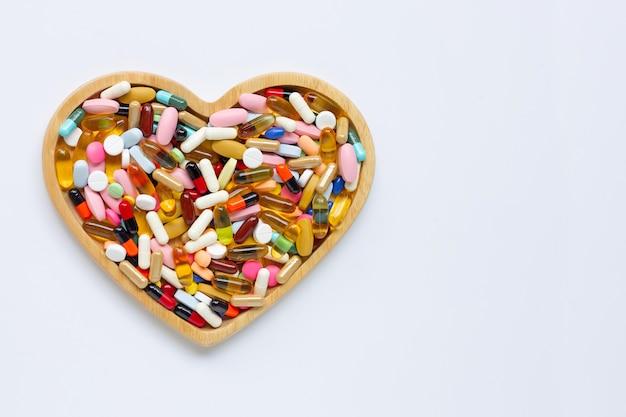 Bunte tabletten mit kapseln und pillen auf weißem hintergrund. hölzerne herzform platte. Premium Fotos