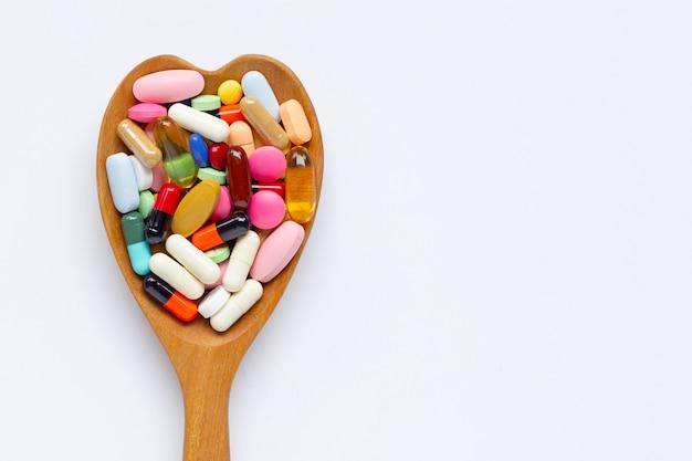 Bunte tabletten mit kapseln und pillen auf weißem hintergrund. hölzerner herzformlöffel. Premium Fotos