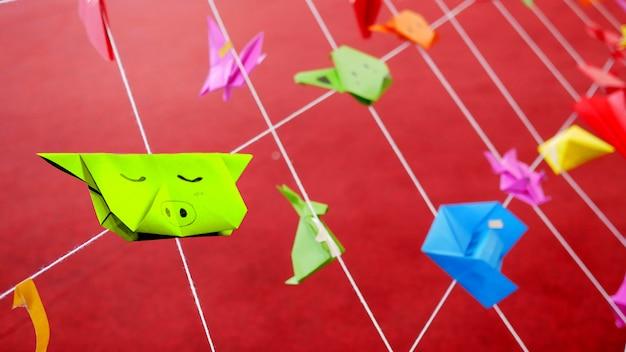 Bunte tierorigamipapiere von den kindern, die mit weißen schnüren im spielplatz der schule hängen. Premium Fotos
