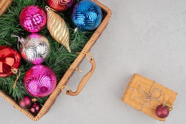 Bunte weihnachtskugeln im korb mit keksen im seil. Kostenlose Fotos