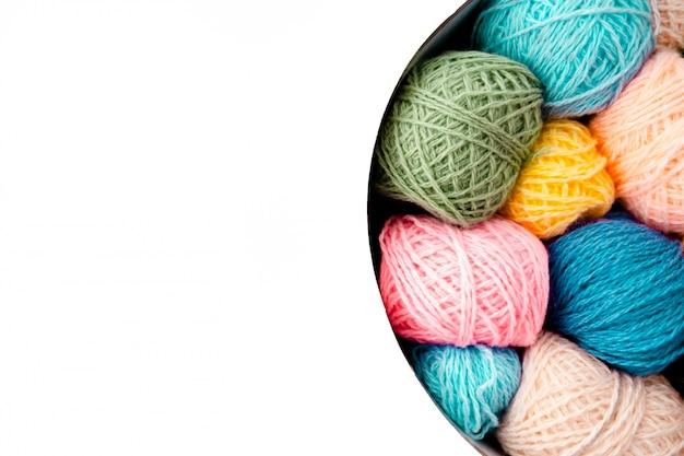 Bunte wollknäuel mit stricknadeln auf weißem hintergrund, hobby und freizeitkonzept. garne zum stricken von copyspace Premium Fotos