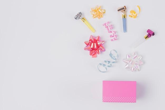 Bunter bandbogen; windenband und schlaghörner über dem rosa kasten gegen weißen hintergrund Kostenlose Fotos
