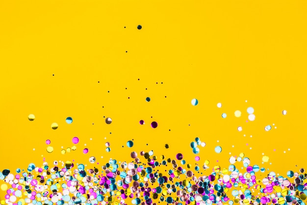 Bunter confetti auf gelbem hintergrund Premium Fotos