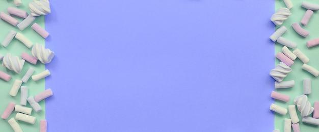Bunter eibisch ausgebreitet auf grünem und lila papierhintergrund Premium Fotos