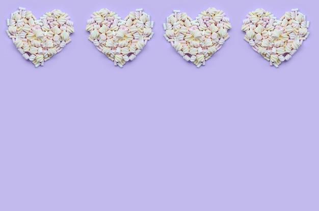 Bunter eibisch ausgebreitet auf violettem und rosa papierhintergrund. Premium Fotos