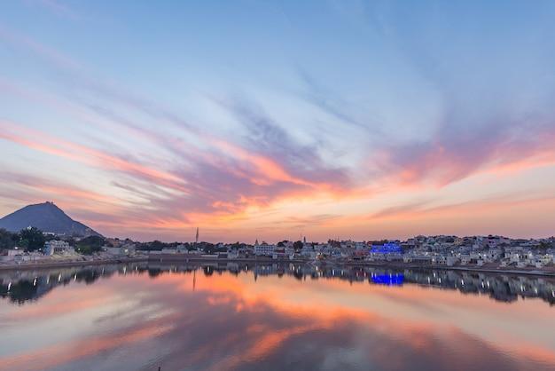 Bunter himmel und wolken über pushkar, rajasthan, indien. tempel, gebäude und farben, die über das weihwasser des sees bei sonnenuntergang nachdenken. Premium Fotos