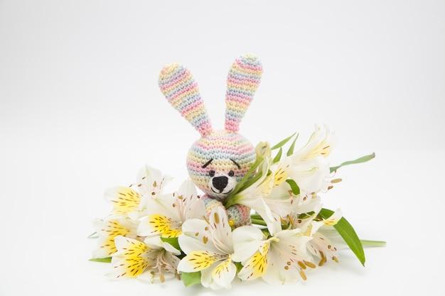 Bunter kleiner hase mit weißen blumen, handgemachtes, gestricktes spielzeug, amigurumi Premium Fotos