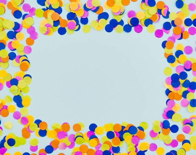 Bunter konfettirahmen auf blauem hintergrund Kostenlose Fotos