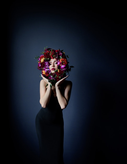 Bunter kreis gemacht von den frischen blumen auf dem gesicht des schönen mädchens, frau gekleidet in schwarzem engem kleid auf dem dunkelblauen hintergrund Kostenlose Fotos