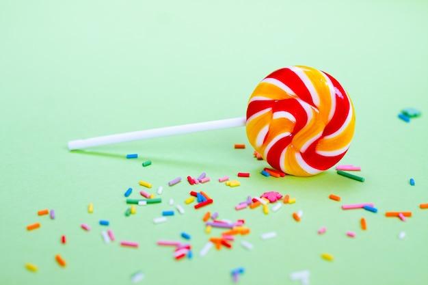 Bunter lutscher und konfetti auf grünem hintergrund. süßigkeiten für die party Premium Fotos