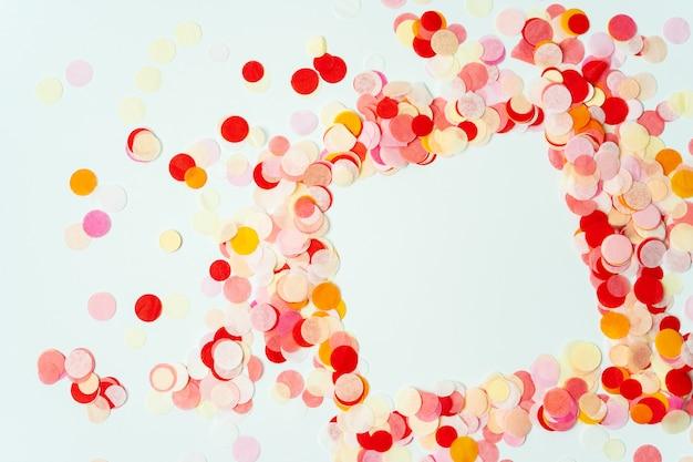 Bunter rahmen gemacht mit roten und orange festlichen konfettis auf pastellhintergrund Premium Fotos