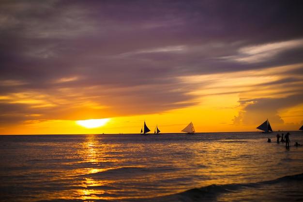 Bunter schöner sonnenuntergang mit segelboot auf dem horizont in boracay-insel Premium Fotos