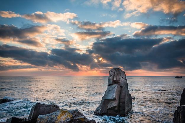 Bunter sonnenaufgang über felsigem strand. Premium Fotos