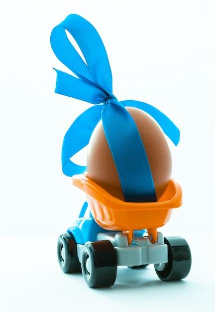 Bunter spielzeuglastwagen mit einer hühnerei in der rückseite auf einem weißen hintergrund Premium Fotos