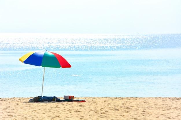 Bunter strandschirm mit einem kissen und einem kleinen kissen auf verlassenem strand an einem sonnigen tag Premium Fotos