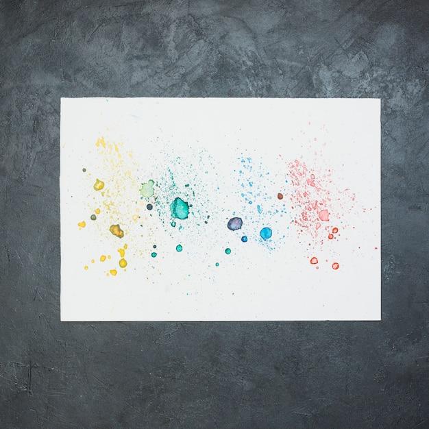 Bunter wasserfarbfleck auf weißbuch über schwarzem hintergrund Kostenlose Fotos