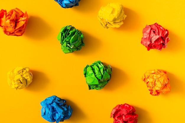 Bunter zerknitterter papierball auf gelbem hintergrund Kostenlose Fotos