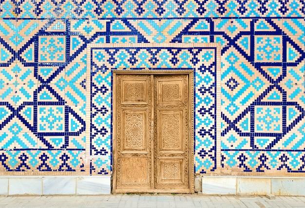 Buntes altes traditionelles usbekmuster auf dem keramikziegel auf der wand der moschee, abstrakter hintergrund Premium Fotos