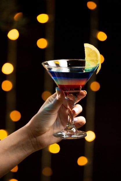 Buntes cocktail mit zitrone in der hand. Kostenlose Fotos