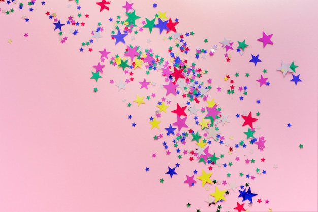 Buntes funkeln spielt dekoration, frohe weihnachten die hauptrolle, das guten rutsch ins neue jahr, das auf rosa hintergrund lokalisiert wird. sternförmiges konfetti Premium Fotos