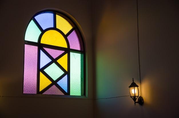 Buntes glasfenster mit lampenlicht auf wand Premium Fotos