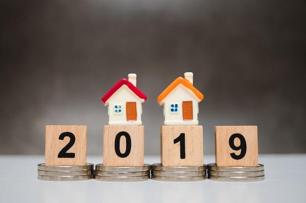 Buntes miniaturhaus auf holzblockjahr 2019 und stapelmünzen unter verwendung als geschäft conce Premium Fotos