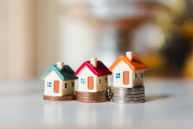 Buntes miniaturhaus auf stapelmünzen unter verwendung als eigentum und finanzkonzept Premium Fotos