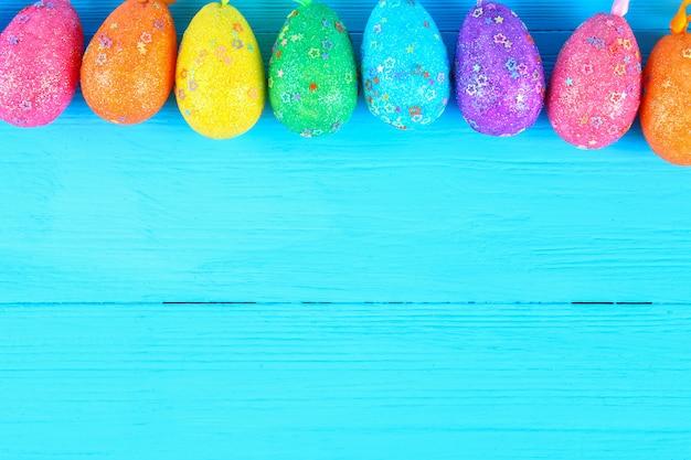 Buntes osterei auf blauem pastellfarbholzhintergrund mit raum Premium Fotos