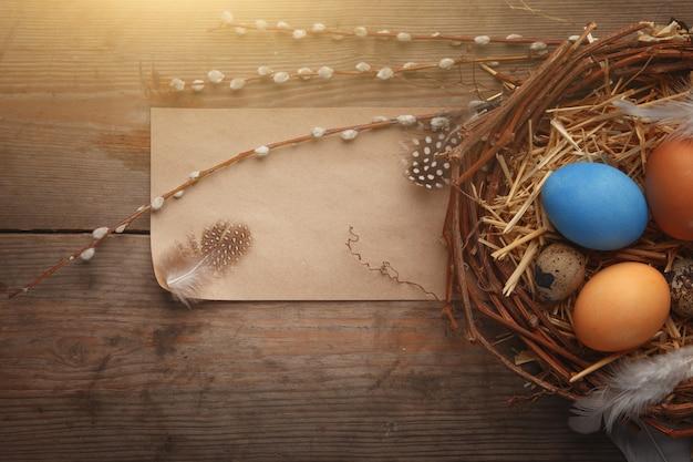 Buntes osterei im nest auf dunklem hölzernem brett. Premium Fotos
