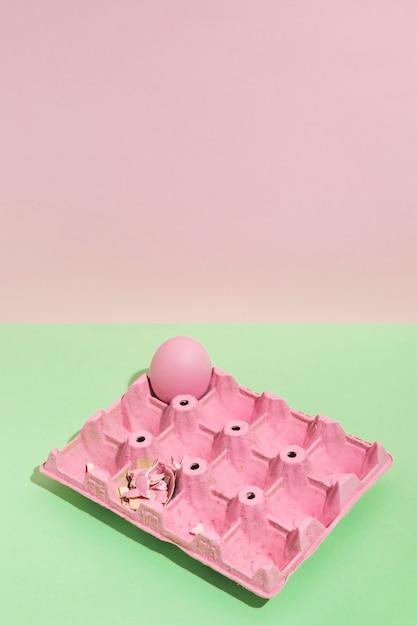 Buntes osterei im rosa gestell auf grüner tabelle Kostenlose Fotos