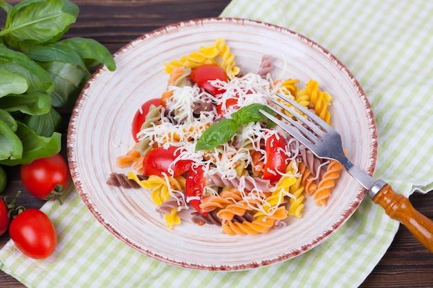Buntes teigwaren fusilli mit tomate, basilikum und käse auf einem dunklen holztisch Premium Fotos