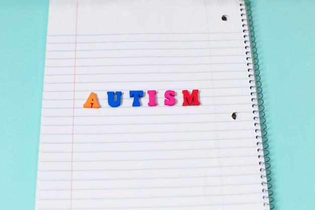 Buntes wort des autismus von den farbhölzernen buchstaben auf notizbuchseite. Premium Fotos
