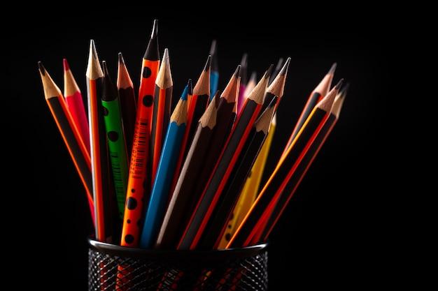 Buntstifte aus graphit zum zeichnen und schreiben in einem schwarzen kleinen korb auf einem schwarzen schreibtisch Kostenlose Fotos