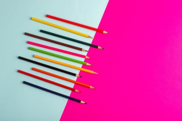 Buntstifte der draufsicht, die auf blauer und rosa schreibtischfarbzeichnungskunstfarbe gezeichnet werden Kostenlose Fotos
