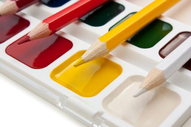 Buntstifte und aquarellfarben isoliert Premium Fotos