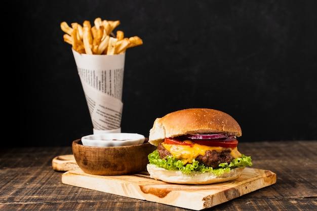 Burger auf schneidebrett mit pommes frites Kostenlose Fotos