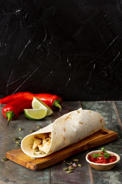 Burrito auf schneidebrett in der nähe von paprika, limette und tomatensauce Kostenlose Fotos