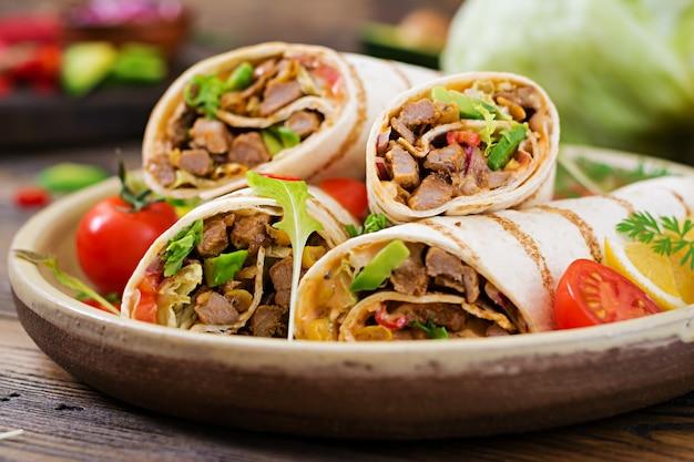 Burritos wraps mit rindfleisch und gemüse auf holz. rindfleisch burrito, mexikanisches essen. gesundes essen hintergrund. mexikanische küche. Premium Fotos
