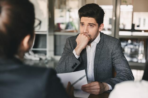 Business-, karriere- und vermittlungskonzept - europäischer mann der 30er jahre beißt sich die faust und macht sich während eines vorstellungsgesprächs im büro mit einer gruppe von spezialisten sorgen Premium Fotos