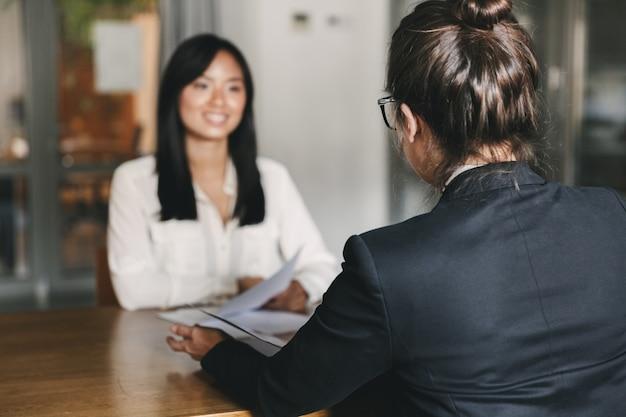 Business-, karriere- und vermittlungskonzept - foto von der rückseite des interviews mit der geschäftsfrau und dem gespräch mit der bewerberin während des vorstellungsgesprächs Premium Fotos