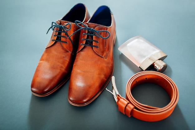 Businessman's zubehör. braune lederschuhe, gürtel, parfüm. männliche mode. geschäftsmann Premium Fotos