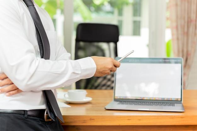 Businessmans-hand, die mobiltelefon mit laptop auf hölzernem schreibtisch hält Premium Fotos
